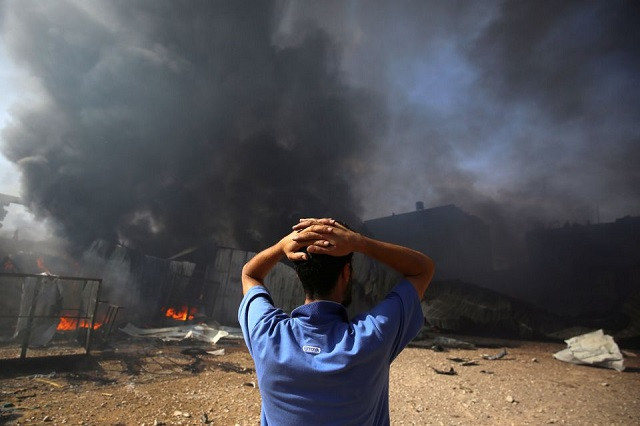 A man stands near a burning sponge factory after it was hit by Israeli artillery shells, according to witnesses, in the northern Gaza Strip May 17, 2021. PHOTO: REUTERS