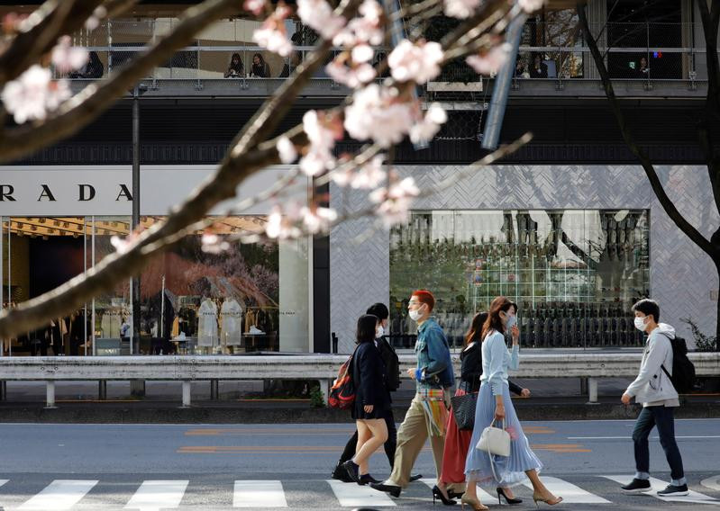 pedestrians wearing protective face masks amid the coronavirus disease covif 19 outbreak are seen behind cherry blossoms in tokyo japan march 18 2021 photo reuters file