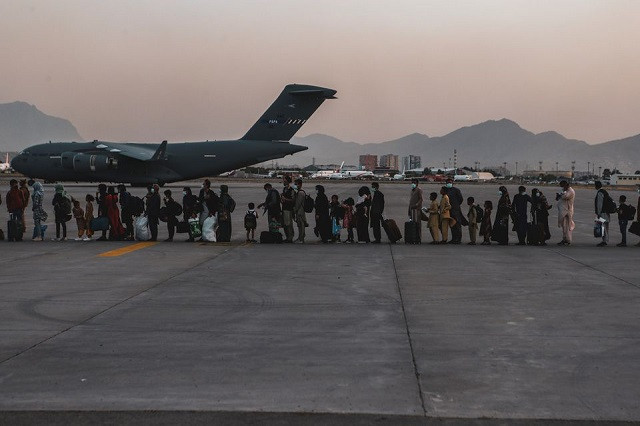 Evacuees wait to board a Boeing C-17 Globemaster III during an evacuation at Hamid Karzai International Airport in Kabul, Afghanistan, August 23, 2021. PHOTO: REUTERS
