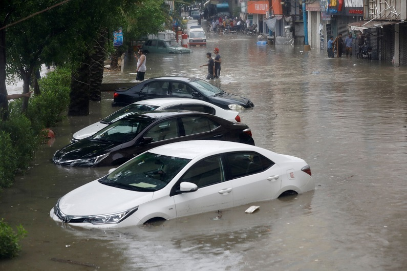 parked vehicles submerged in rainwater on a road in karachi photo express
