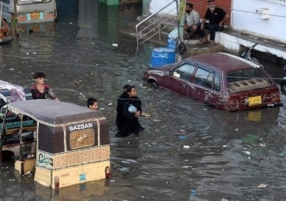 people wade through a flooded street after heavy monsoon rains in karachi on july 27 photo afp file