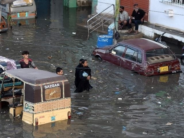 People wade through a flooded street after heavy monsoon rains in Karachi on July 27. PHOTO: AFP/FILE