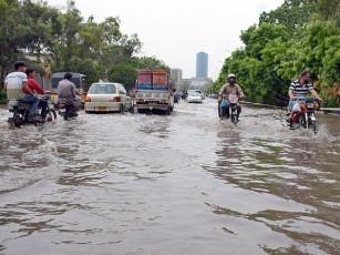 Vehicles pass through rain water accumulated near Governor House after heavy rain in Karachi. PHOTO: APP