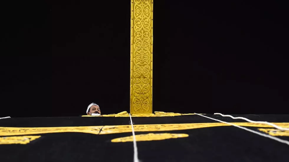 A Saudi worker adjusts the new Kiswah, the gold-embroidered black cloth covering the Kaaba, that is changed during each year's Hajj. PHOTO: AFP