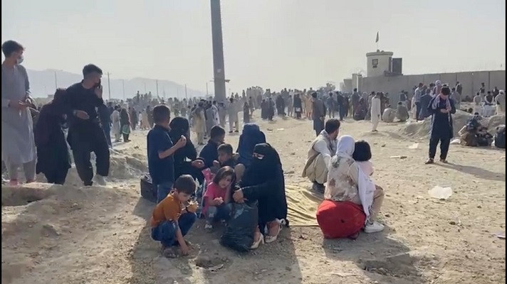 People gathered outside the airport react to gunfire, in Kabul, Afghanistan August 18, 2021 in this still image taken from video. PHOTO: REUTERS