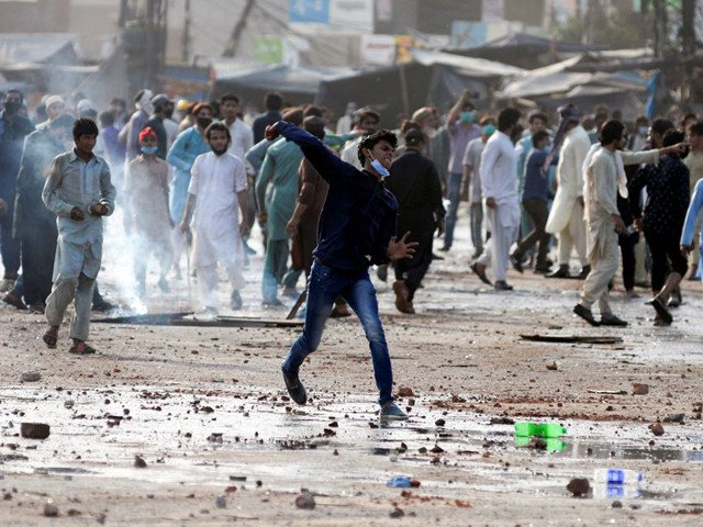 a supporter of tlp hurls stones towards police during a protest in lahore photo reuters file