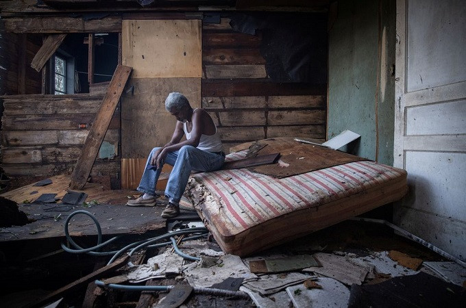 Theophilus Charles, 70, sits inside his house which was heavily damaged by Hurricane Ida in Houma, Louisiana, U.S., August 30, 2021. REUTERS/Adrees Latif