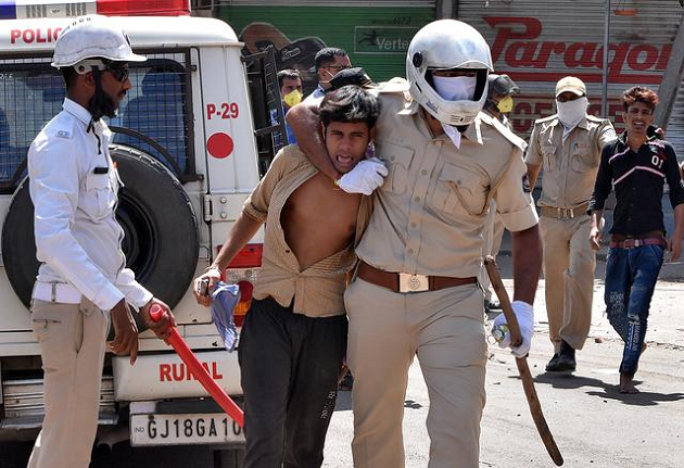 police officers detain men during a protest by migrant workers demanding to return to their home states in surat photo reuters file