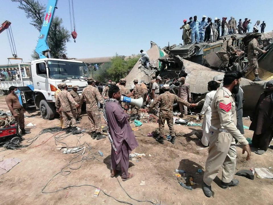 Paramilitary soldiers and rescue workers gather at the site following a collision between two trains in Ghotki, Pakistan June 7, 2021. Inter-Services Public Relations (ISPR)/ Handout via REUTERS ATTENTION EDITORS - THIS PICTURE WAS PROVIDED BY A THIRD PARTY. NO RESALES. NO ARCHIVE.