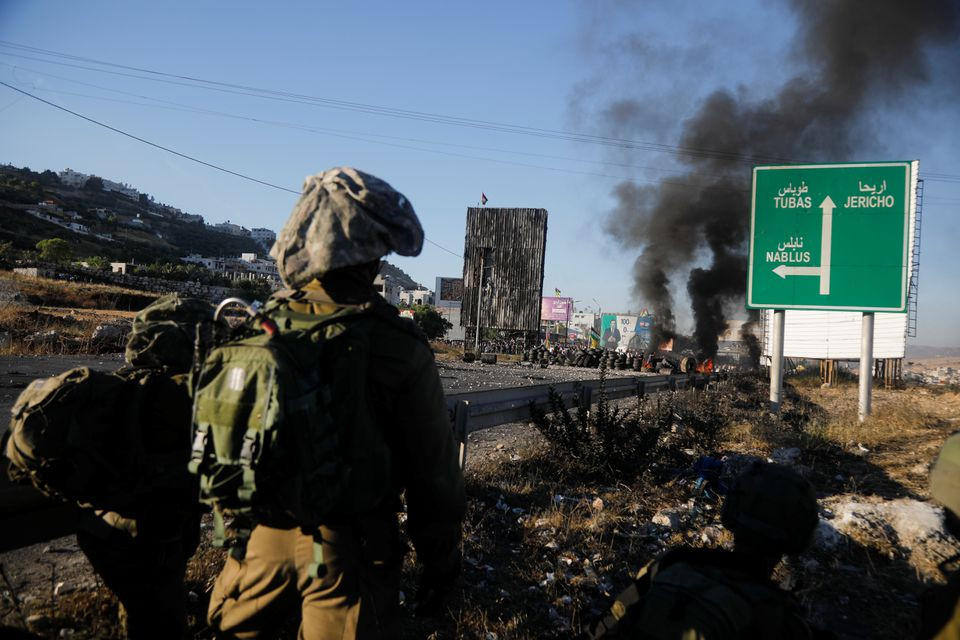 Israel's soldiers look on during an anti-Israel protest over cross-border violence between Palestinians in Gaza and the Israeli military, near Hawara checkpoint near Nablus in the Israeli-occupied West Bank, May 18, 2021. PHOTO: REUTERS