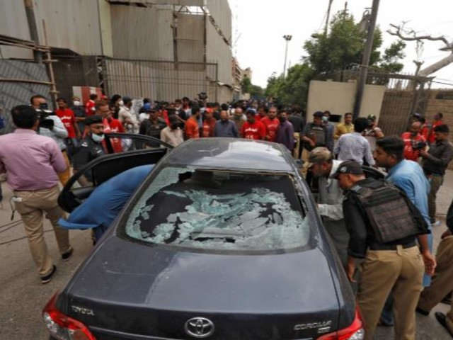 Police officers survey a damaged car at the site of an attack at the Pakistan Stock Exchange (PSX) entrance in Karachi. PHOTO: REUTERS