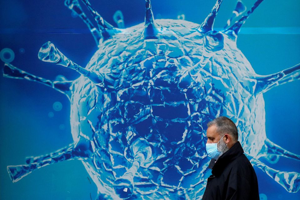 a man wearing a protective face mask walks past an illustration of a virus outside a regional science centre amid the coronavirus disease covid 19 outbreak in oldham britain photo reuters
