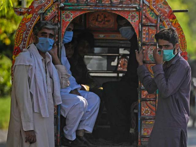Passengers wearing facemasks wait next to a vehicle in Islamabad. PHOT: AFP