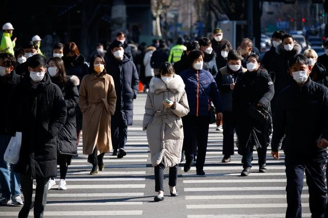 commuters cross a zebra crossing amid the coronavirus disease covid 19 pandemic in seoul south korea february 3 2021 photo reuters