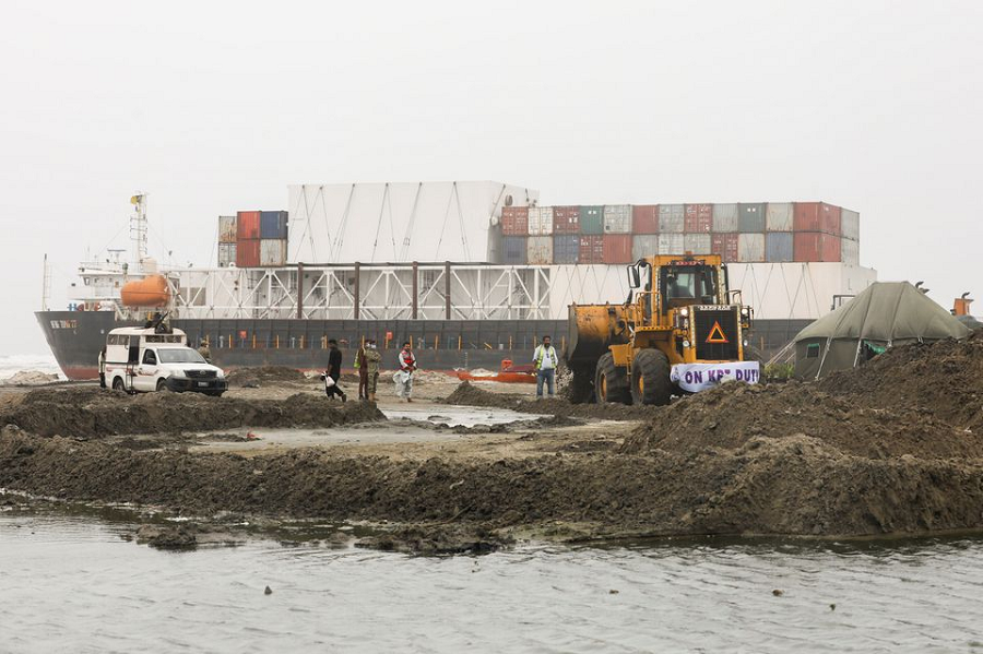 A wheel loader clears the ground near stranded cargo ship MV Heng Tong 77 at Sea View beach in Karachi. PHOTO: REUTERS