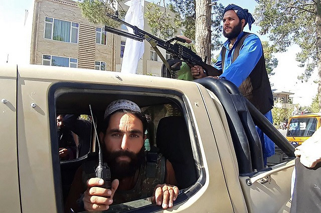 Taliban fighters are pictured in a vehicle along the roadside in Herat, Afghanistan's third biggest city, after government forces pulled out following weeks of being under siege. Photo: AFP