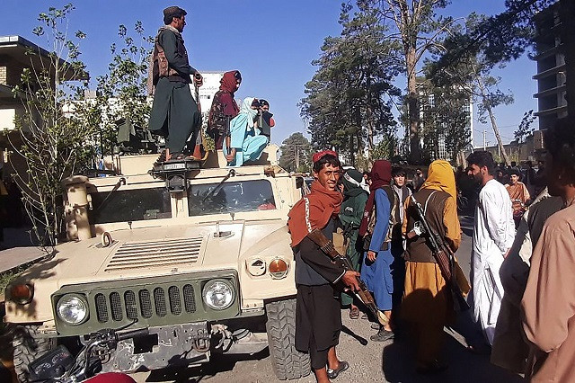 Taliban fighters stand guard along the roadside in Herat, Afghanistan's third biggest city, after government forces pulled out following weeks of being under siege. Photo: AFP