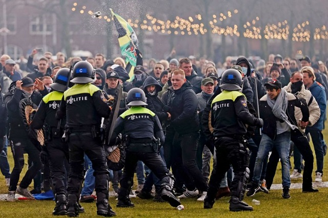 riot police clash with protesters during a demonstration in the museumplein town square in amsterdam on jan 17 2021 photo afp