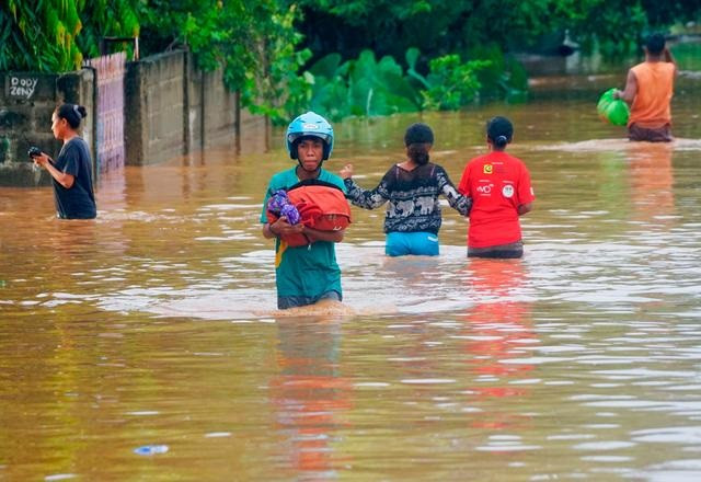 A man wearing a helmet carries his goods through the water in an area affected by floods after heavy rains in Dili, East Timor, April 4, 2021. PHOTO: REUTERS