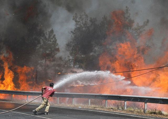 A firefighter tries to extinguish a wildfire near Marmaris, Turkey, August 1, 2021. PHOTO: REUTERS