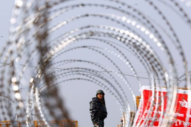 police officer in riot gear stands guard behind concertina wire at a protest against farm laws at the delhi uttar pradesh border in ghaziabad india february 3 2021 photo reuters