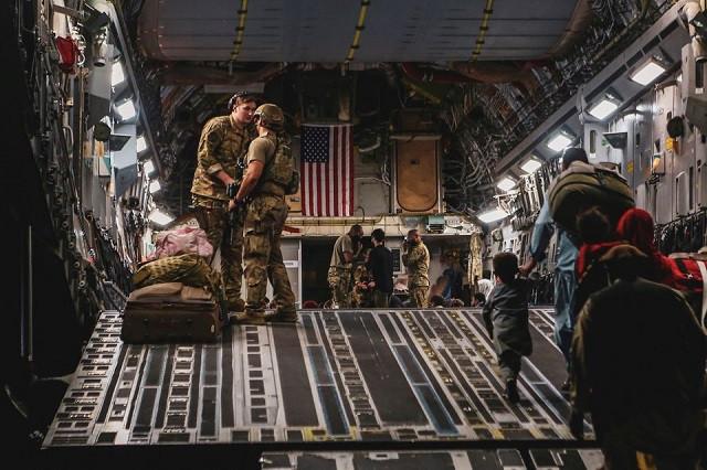 Evacuees board a Boeing C-17 Globemaster III during an evacuation at Hamid Karzai International Airport in Kabul, Afghanistan, August 23, 2021. PHOTO: REUTERS