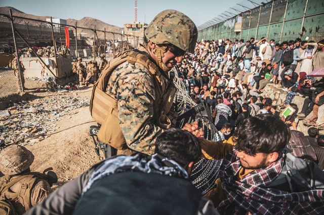 A US Marine assists at an Evacuation Control Check Point (ECC) during an evacuation at Hamid Karzai International Airport, Kabul, Afghanistan, August 26, 2021. PHOTO: REUTERS