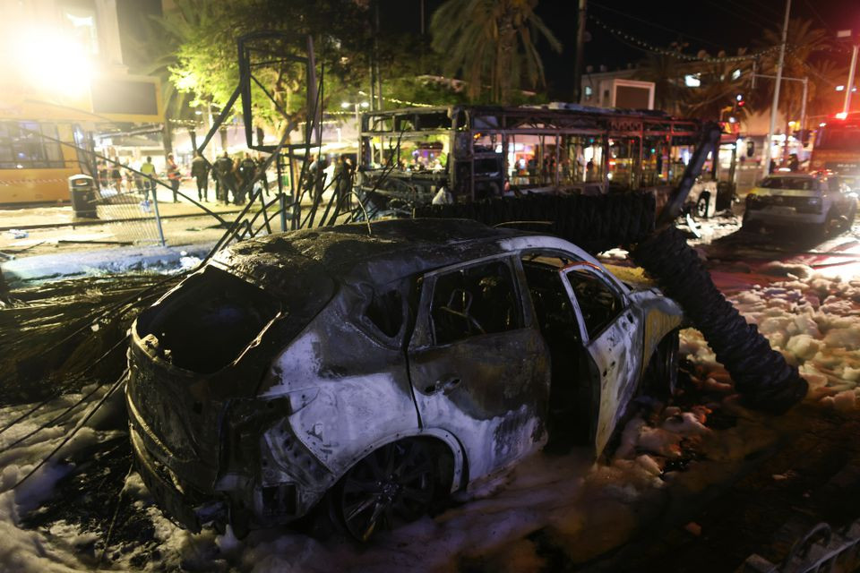 Burnt vehicles are seen at the scene where a rocket launched from the Gaza Strip hit, in Holon, Israel May 11, 2021. PHOTO: REUTERS