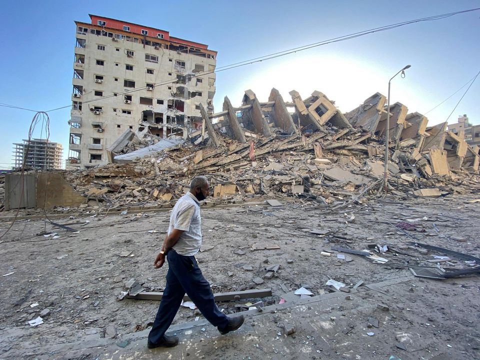 A Palestinian man walks past a tower building which was destroyed in Israeli air strikes, amid a flare-up of Israeli-Palestinian violence, in Gaza City May 12. PHOTO: REUTERS
