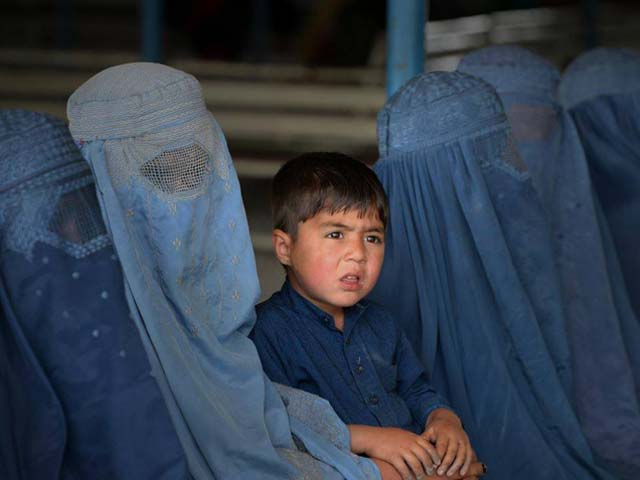 Afghan refugee families wait to be registered at the UNHCR repatriation centre. PHOTO: AFP