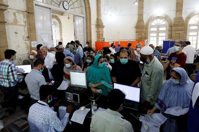 people gather for their coronavirus disease covid 19 vaccine doses at a vaccination centre in karachi pakistan march 22 2021 photo reuters