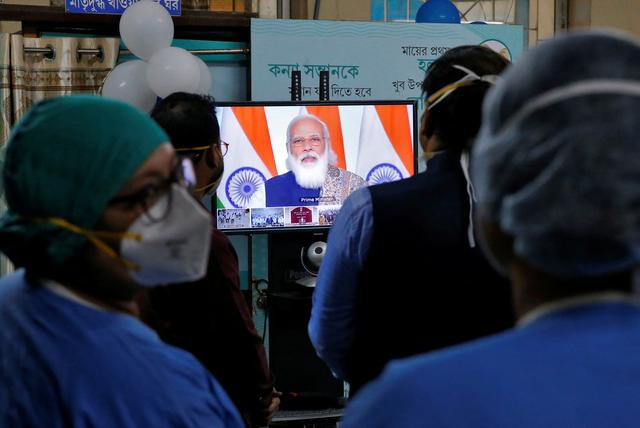 healthcare workers watch indian prime minister narendra modi addressing them through video conferencing to launch one of the world s largest covid 19 vaccination campaigns at a government run hospital in kolkata india january 16 2021 reuters
