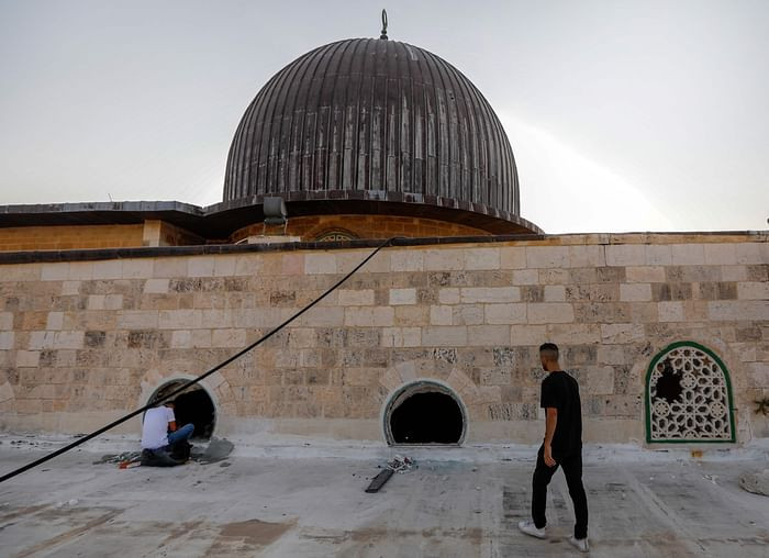 Palestinian youths look into the Al-Aqsa mosque on the first day of the Eidul Azha feast celebrated by Muslims worldwide, on July 20, 2021, through windows which were shattered two days earlier in renewed clashes between Palestinians and Israeli police at the Al-Aqsa complex in Jerusalems old city. PHOTO: AFP
