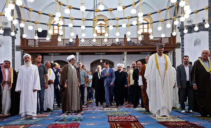 A handout picture released by the official Facebook page of the Syrian Presidency shows President Bashar al-Assad (C) performing Eidul Azha prayer at Khaled bin al-Walid mosque in Homs on July 20, 2021. PHOTO: AFP