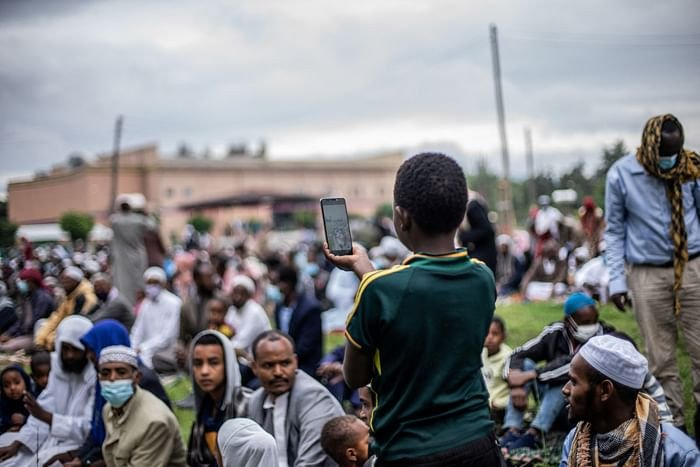 A muslim boy takes pictures during the Eidul Azha prayers on the first day of the feast celebrated by Muslims worldwide, at the Millennium Square in Hawassa, Ethiopia, on July 20, 2021. PHOTO: AFP