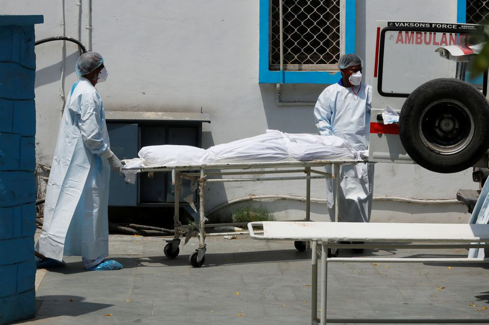 Mortuary workers load the body of a person, who died from the coronavirus disease (COVID-19), to an ambulance for cremation, at a hospital in New Delhi, India May 5, 2021. REUTERS