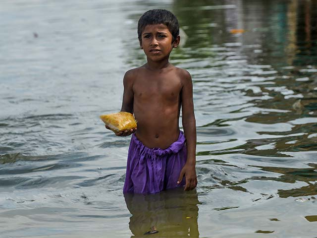 a boy wades through a flooded street in karachi photo afp