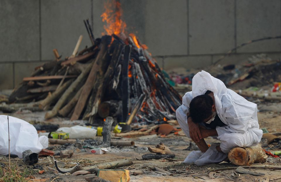 A man mourns as he sits next to the burning pyre of a relative, who died from the coronavirus disease (COVID-19), during his cremation, at a crematorium in New Delhi, India May 5, 2021. REUTERS