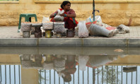 A dry fruit vendor waits for customers alongside a street inundated with rainwater in Karachi. PHOTO: AFP
