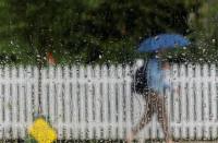 A pedestrian under an umbrella passes a rain covered car window. PHOTO: REUTERS