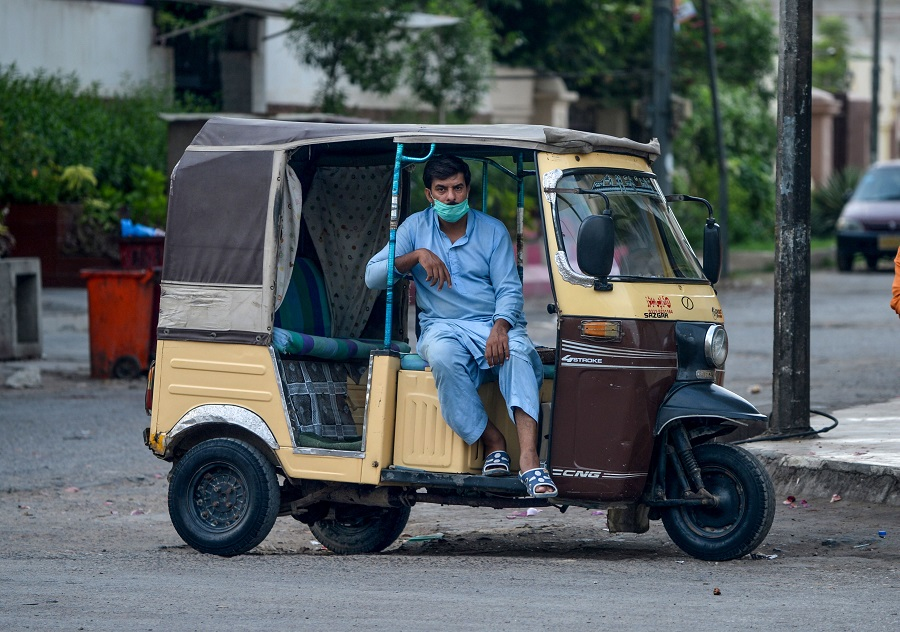 a man sits in his rickshaw with a loosely worn mask photo afp