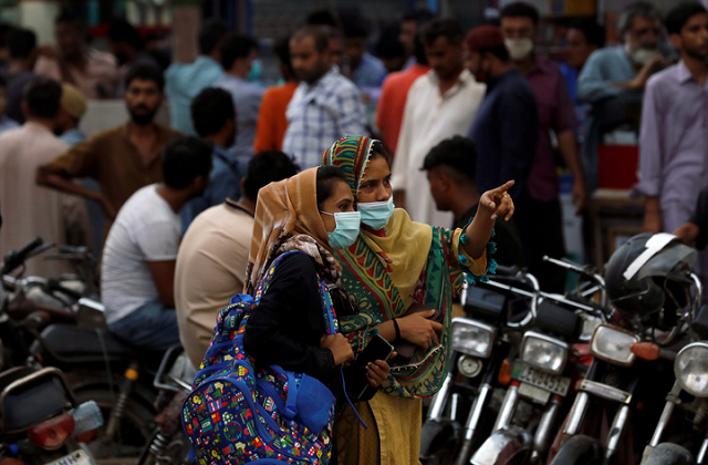 Women wearing protective face masks talk outside a market, as the coronavirus disease (COVID-19) pandemic continues, in Karachi. PHOTO: REUTERS/FILW